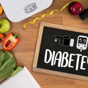 Word Diabetes written on a black slate on a table surrounded by fruits, veggies, bathroom scale, measuring tape and a notebook