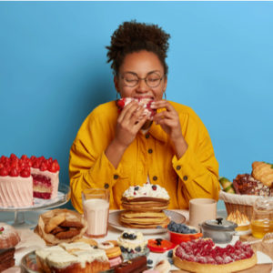 Picture of a lady in yellow shirt and spectacles enjoying large quantities of sugary food placed on the table with her eyes closed