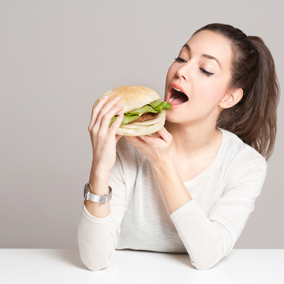 Lady in white t shirt trying to eat a burger with her mouth wide open