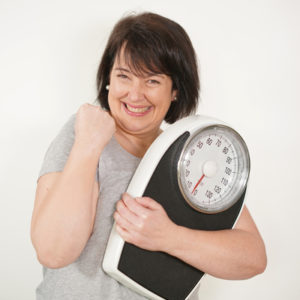 Happy lady showing clenched fist hand gesture carrying a bathroom scale on the other hand for her weight loss